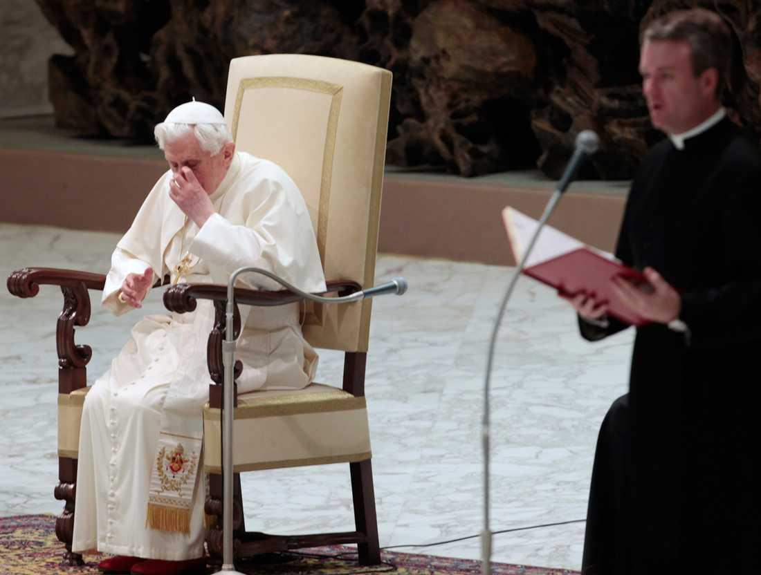 Påven kliar sig på näsan.