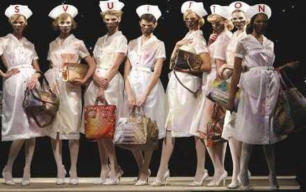 Modeller i genomskinliga sjuksköterskeuniformer på Louis Vuittons visning. På hättorna stavades modehusets namn ut.