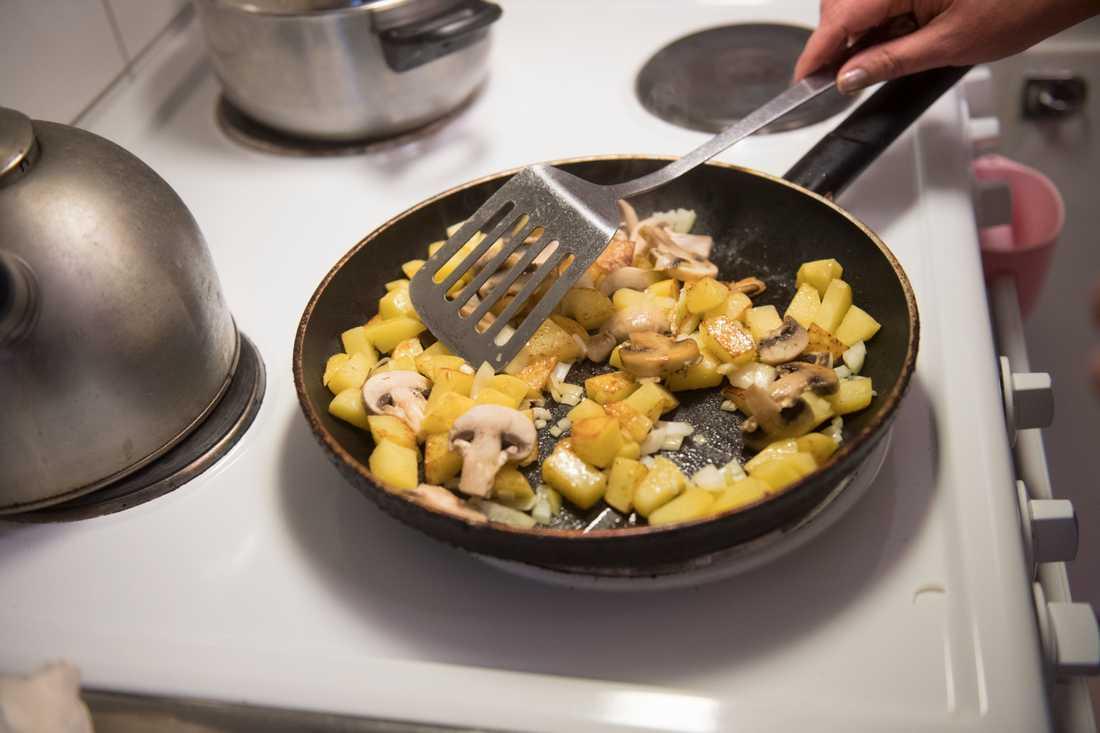 Vegansk stroganoff med potatis, champinjoner, gul lök och broccoli. Arkivbild.