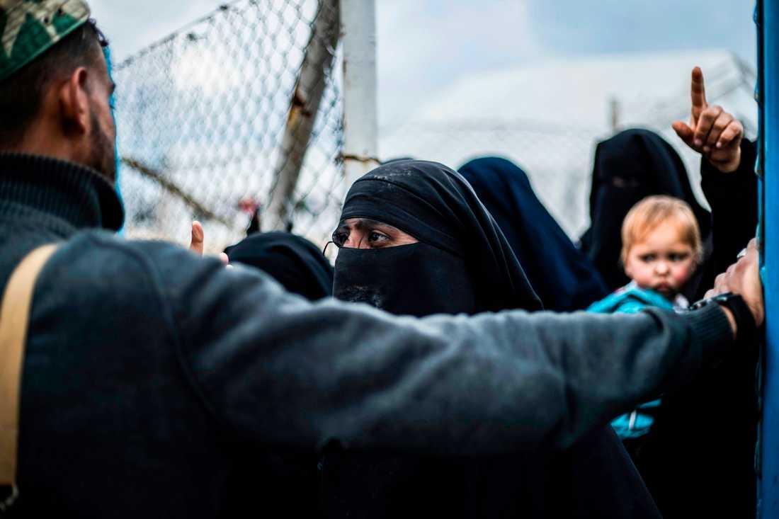 En medlem av den kurdiskdominerade styrkan SDF står vakt i lägret al-Hol i Syrien där anhöriga till IS-män hålls inspärrade.