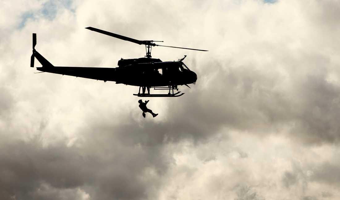 En man från San Bernardino County Sheriffs räddningsteam hissas upp till en helikopter efter att ha räddat tre personer och en hund i Santa Ana-floden.