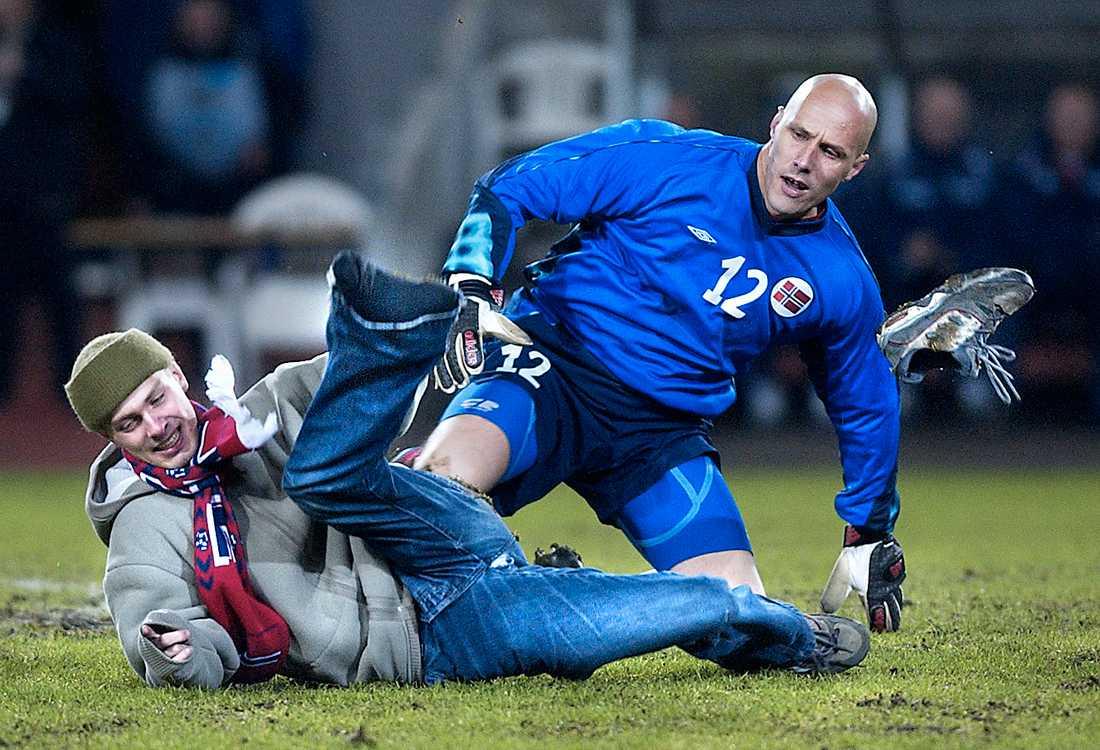 1de4650f Norska supportern Henrik Hægeland tacklas omkull av landslagsmålvakten  Frode Olsen.