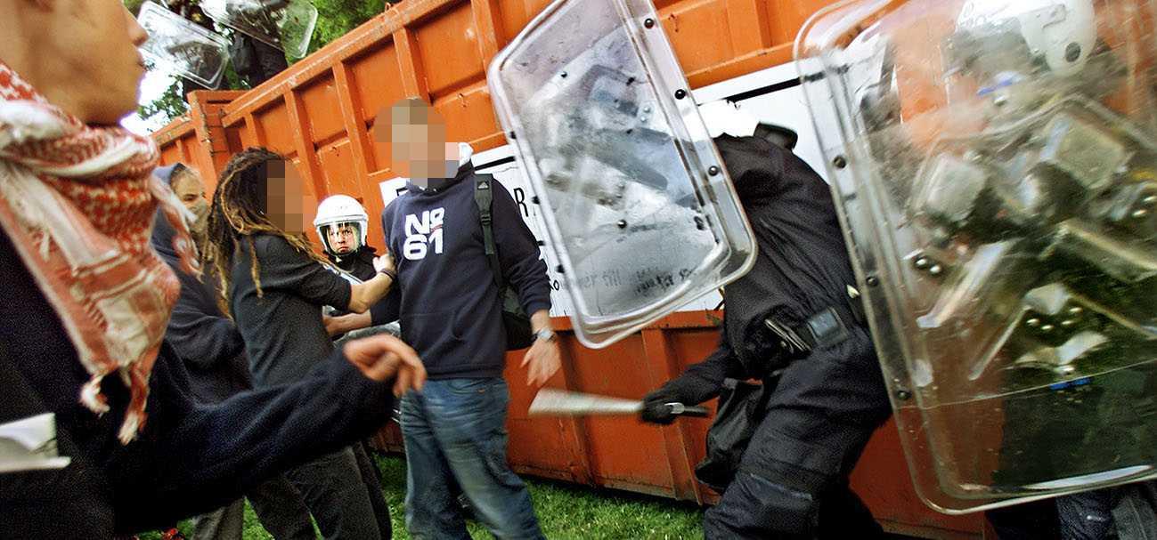 Polis slår med batong mot demonstrant utanför Hvidfeldtska gymnasiet, i juni 2001.