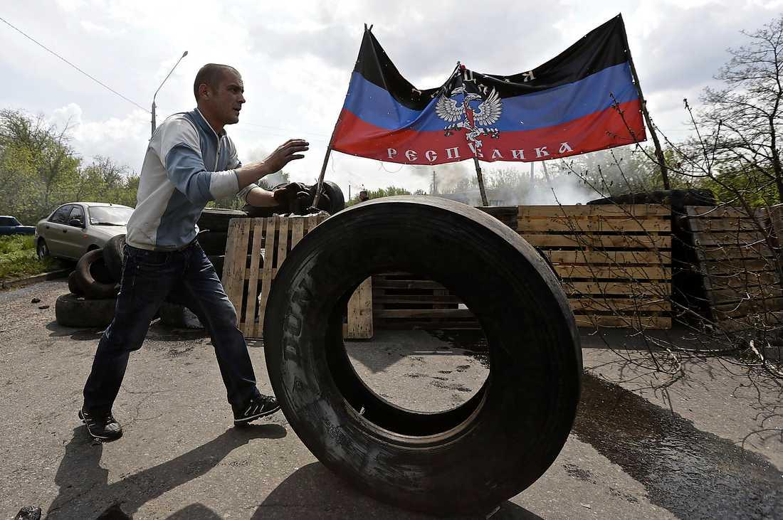 Belägrade städer Vägspärrsbygge i Kramatorsk. I bakgrunden Folkrepubliken Donetsks flagga.
