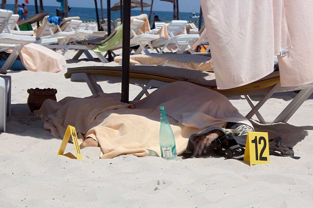 En dödad turist ligger under ett skynke på stranden i Sousse.