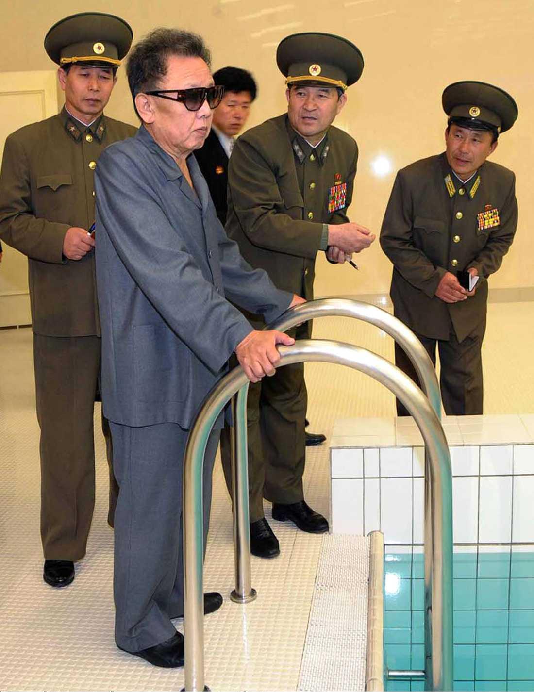 KIM TITTAR PÅ VATTEN Kim Jong Il inspekterar den nya bassängen på universitetet i Pyongyang. Likt Mao Zedong i Kina är även Kim Jong Il en simmare i världsklass.