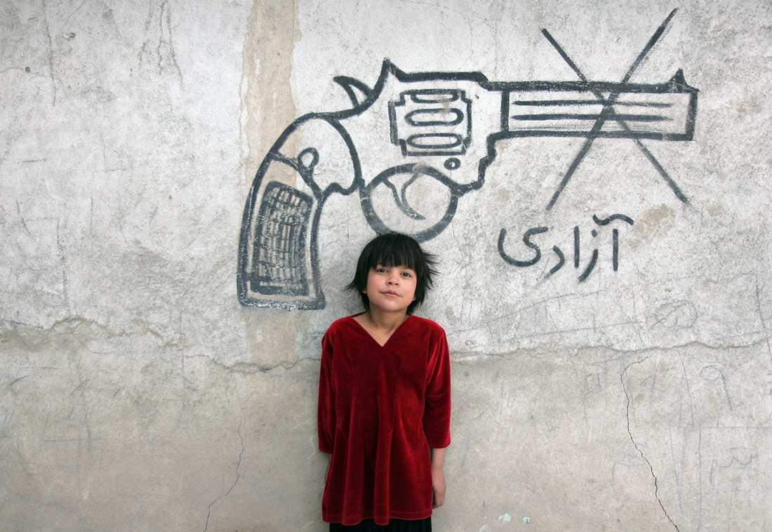 """Ett barn syns bredvid en väggmålning med ordet """"frihet"""", i Afghanistans huvudstad Kabul. Arkivbild."""