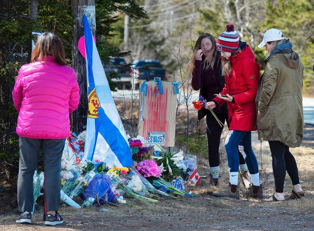 Människor hedrar offren vid en spontan minnesplats i Portapique i Nova Scotia.