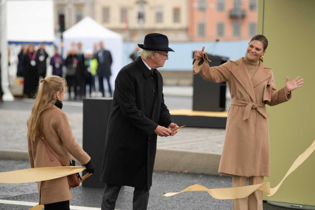 Kung Carl Gustaf, kronprinsessan Victoria och prinsessan Estelle klipper bandet vid Slussbron som förbinder Gamla stan med Södermalm.
