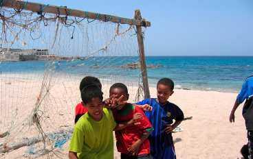 Småkillarna i Mirbat kickar boll på stranden. En ihopsnickrad ställning med fisknät är en perfekt målbur.