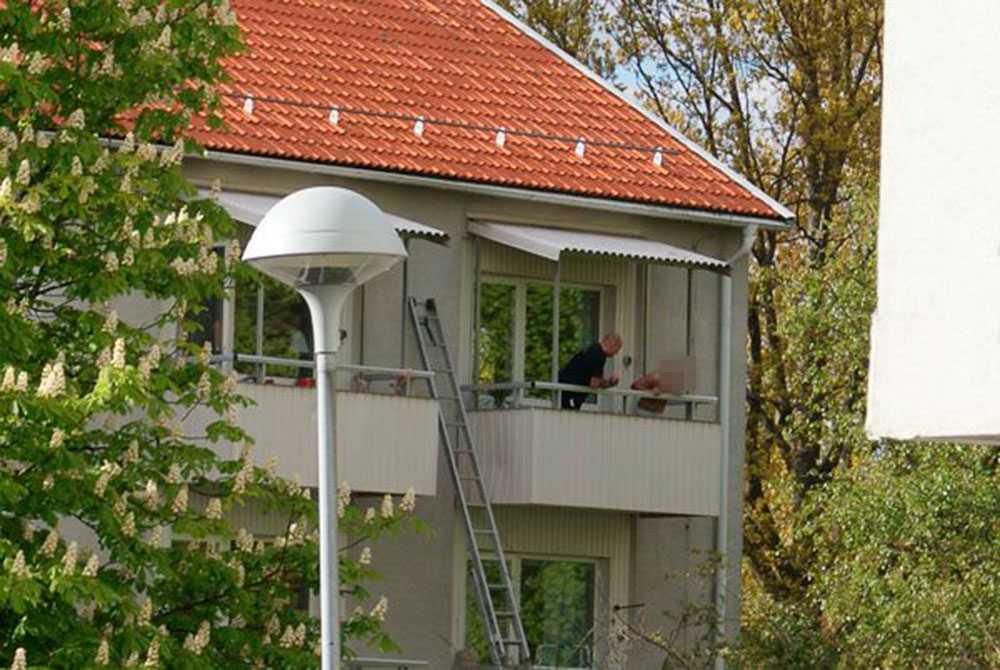 Mannen på balkongen tillsammans med en förhandlare från polisen.