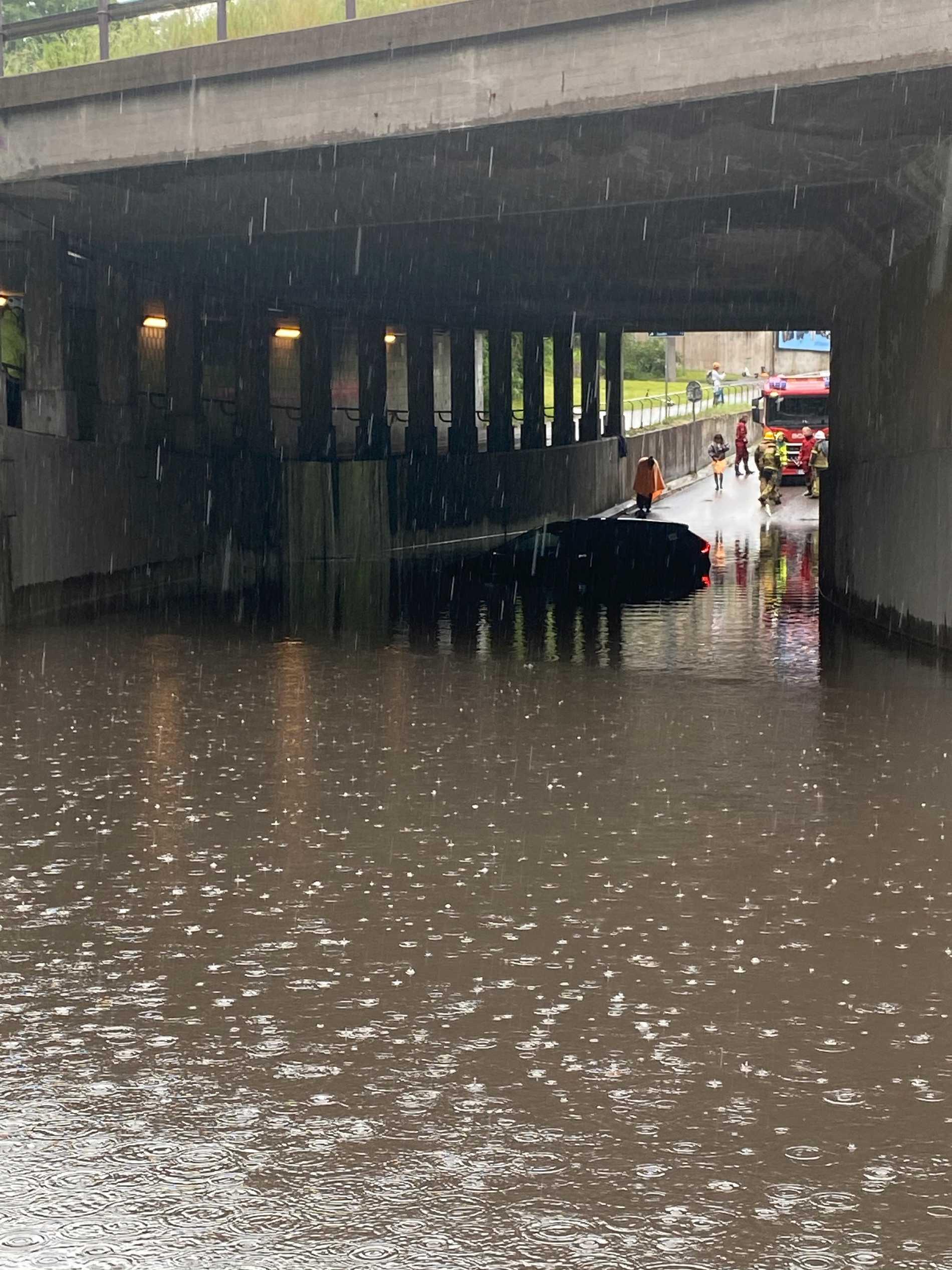 I en tunnel i Liljeholmen har en bil fastnat i vattenmassorna.