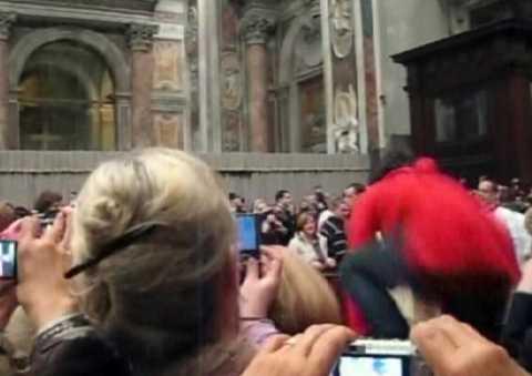 1 Kvinnan, i röd jacka, tog sig över staketet när påven gick fram mot altaret.