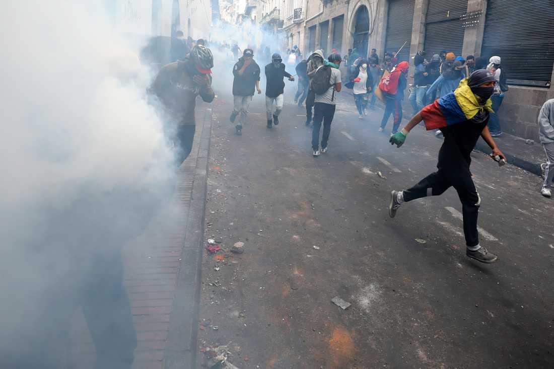 Demonstranter tar skydd undan tårgas.