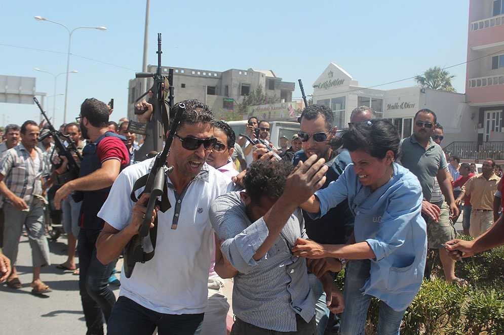Polisen försöker mota bort allmänheten medan de för iväg en misstänkt gärningsman.