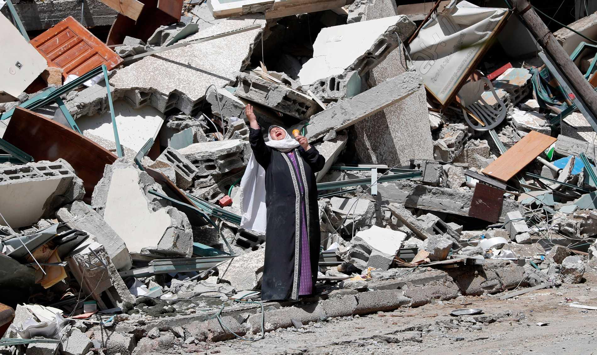 En kvinna gråter under söndagens uppröjning i Gaza efter lördagens attacker.