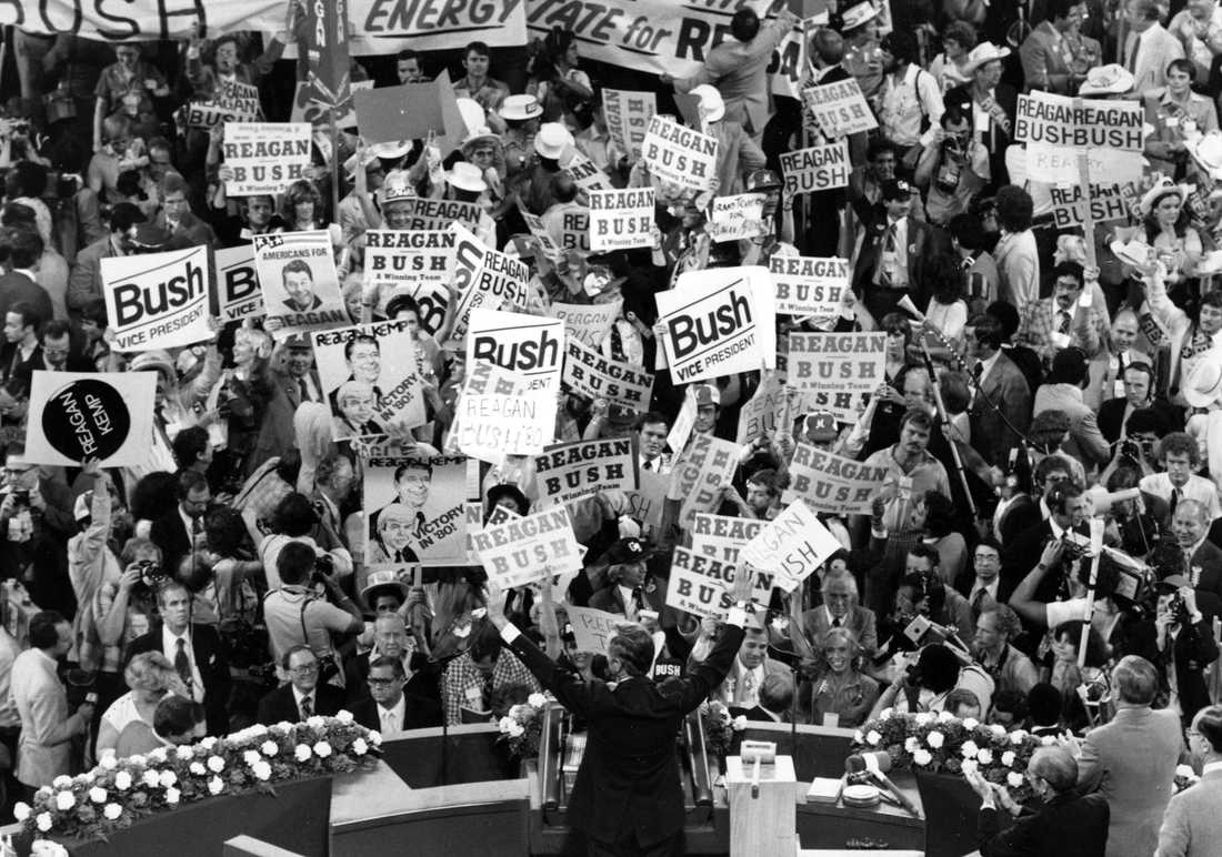 In this July 16, 1980 file photo George H.W. Bush, center foreground, acknowledges the crowd before speaking to the Republican Convention delegates in Detroit, Mich.