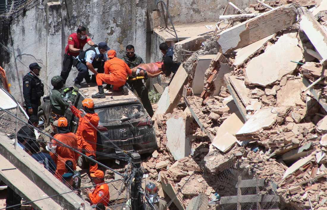 En kvinna bärs ut ur huset som fallit samman i Fortaleza, huvudstad i delstaten Ceará.