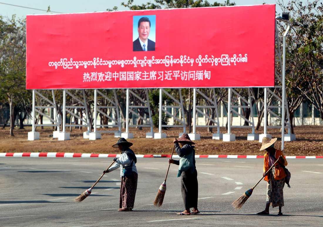 Gatan sopas framför en stor banderoll som välkomnar Xi Jinping till Myanmar.