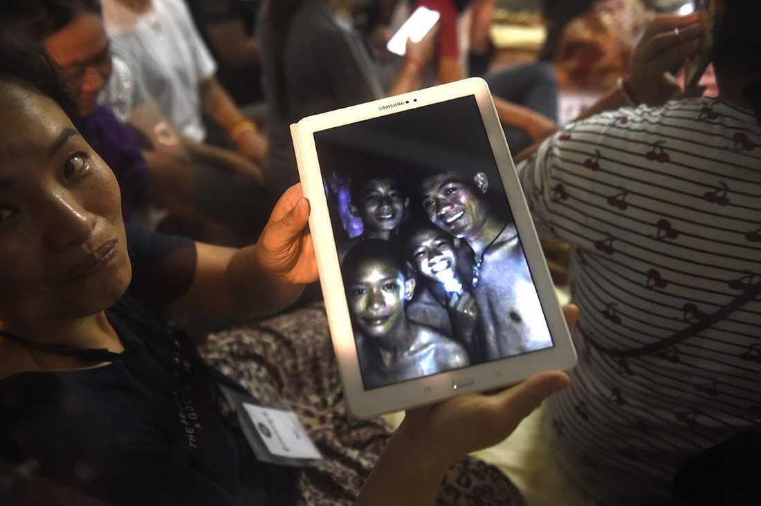 En lycklig familjemedlem håller upp en bild tagen av en räddningsarbetare.