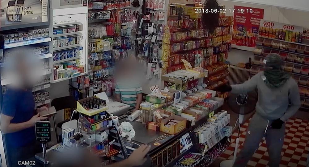 Rånaren hotar personalen med kniv och ett pistolliknande föremål.