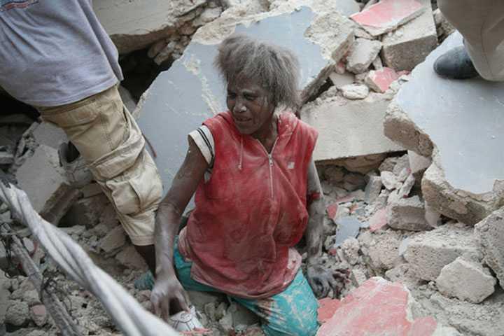 Fast i rasmassorna Otaliga haitier har skadats och fastnat under rasmassorna från byggnader. Här får en kvinna hjälp att ta sig upp.