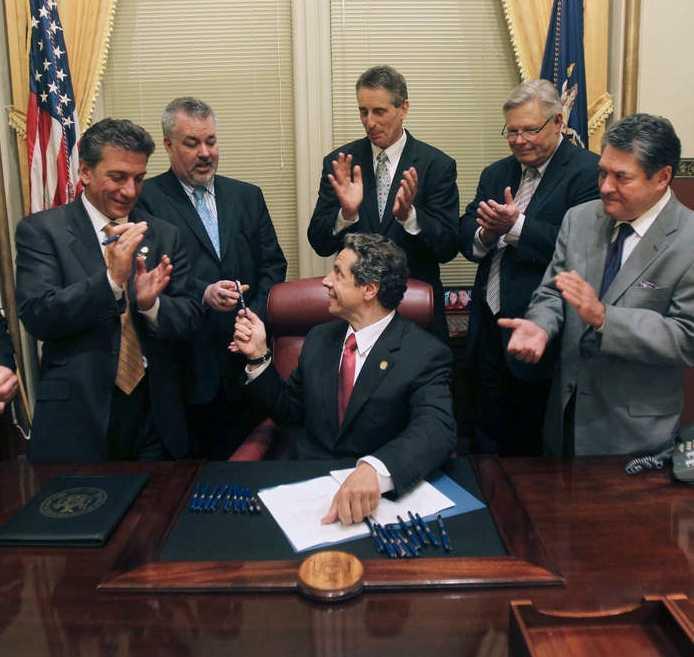 Historisk underskrift New Yorks guvernör, Andrew Cuomo, räcker över pennan efter att ha skrivit under lagen som ger samkönad rätt att ingå äktenskap. Bakom Cuomo, från vänster till höger, står Matthew Titone, Daniel O'Donnell, Robert Duffy, Thomas Duane och James Alesi.