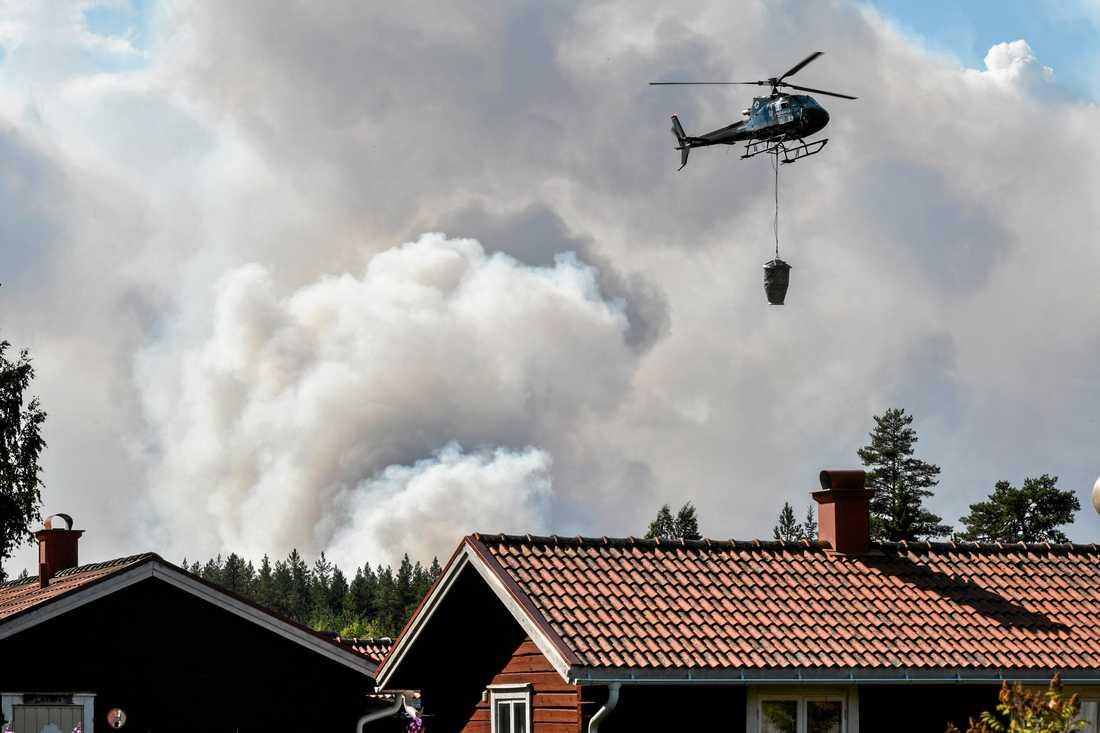 En helikopter hjälper till med släckningsarbetet vid en skogsbrand nära Färila, Ljusdal.