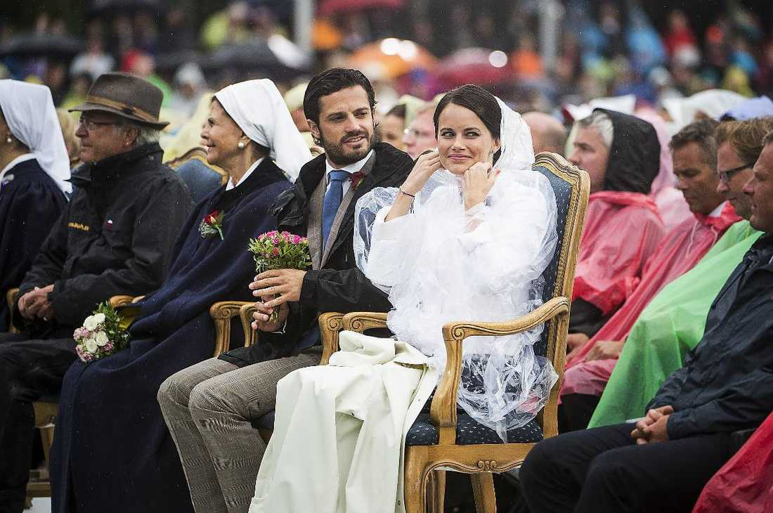 Prins Carl Philip och Sofia Hellqvist myser i regnet.