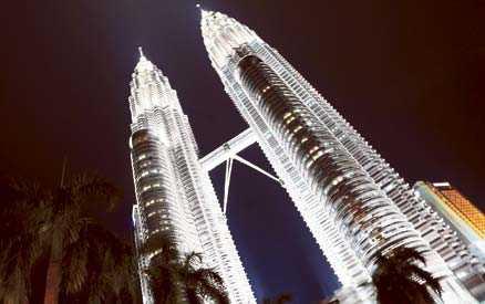 Tvillingtornen Petronas towers reser sig mäktigt i kvällsbelysningen. Tornen var en gång världens högsta byggnad och de är fortfarande ett landmärke i Kuala Lumpur.