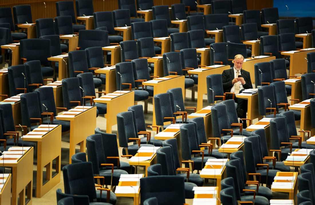 Liberalernas Johan Persson tittar i telefonen.
