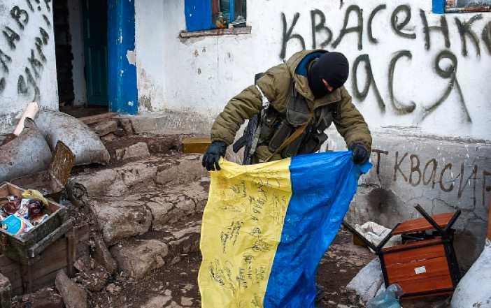 Brödrakriget En prorysk rebell med en ukrainsk flagga vid en erövrad militärpostering i östra Ukraina.