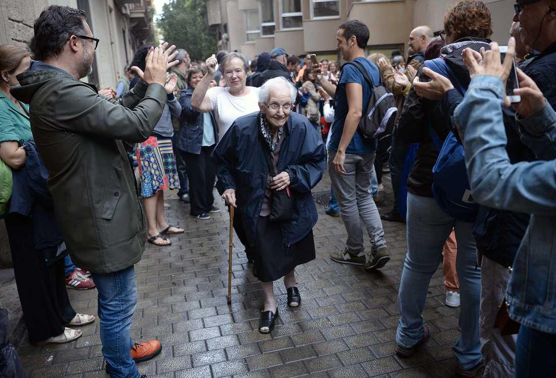 Människor vid en vallokal applåderar en äldre kvinna som varit och röstat.