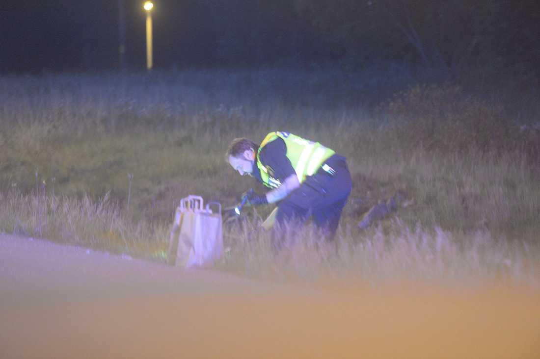Polisen letar efter något i vägrenen vid vid avfarten till E18 vid Bro.