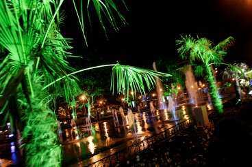 Lyktorna reflekteras i vattenkaskaderna i skymningen vid huvudtorget.