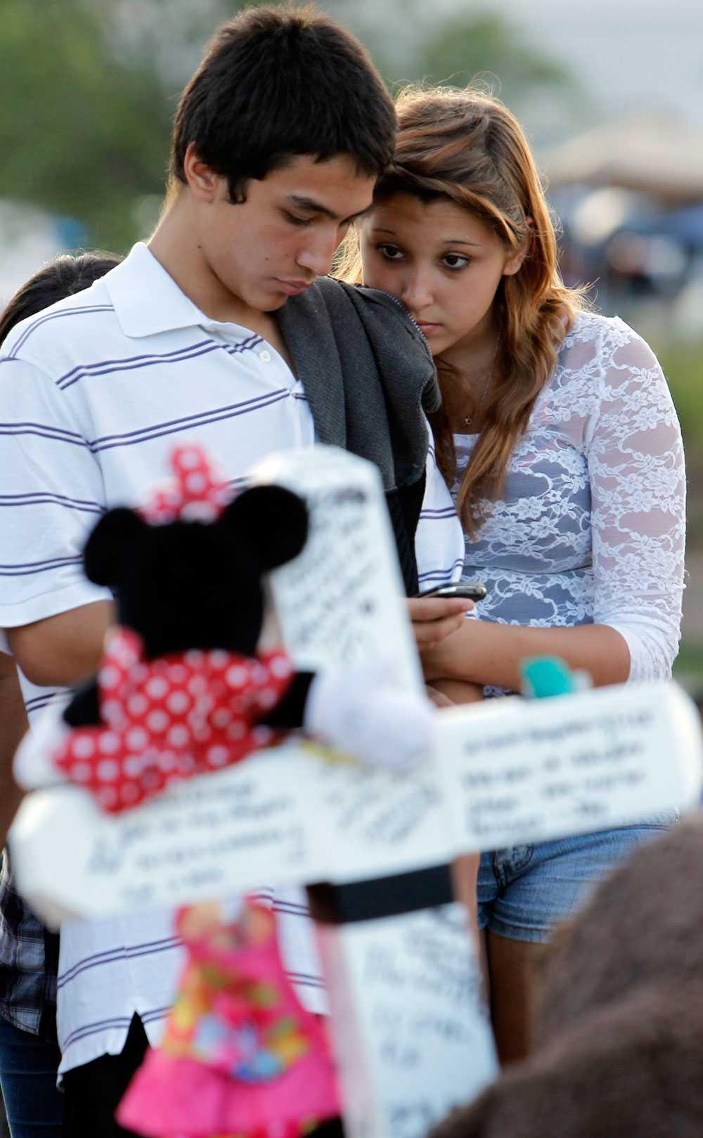 Jovandy Juarez och Angelica Chacon-Valdez tröstar varandra under en minnesceremoni för offren i Aurora.