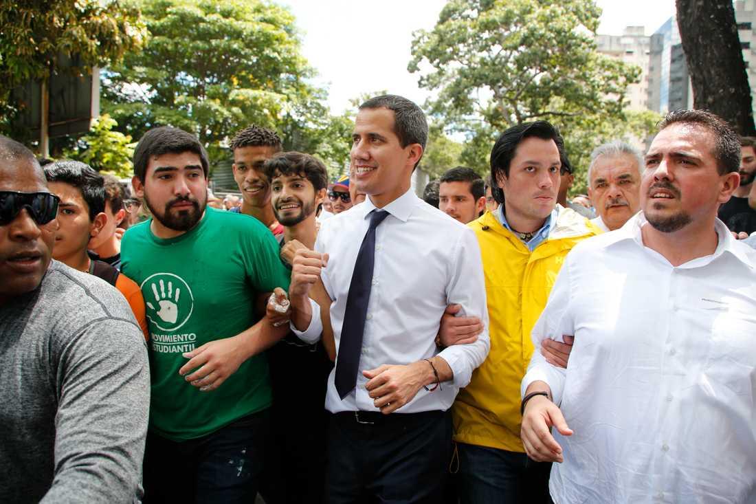 Venezuelas oppositionsledare Juan Guaidó (i vid skjorta och mörk slips) under ett manifestation i Caracas i fredags.