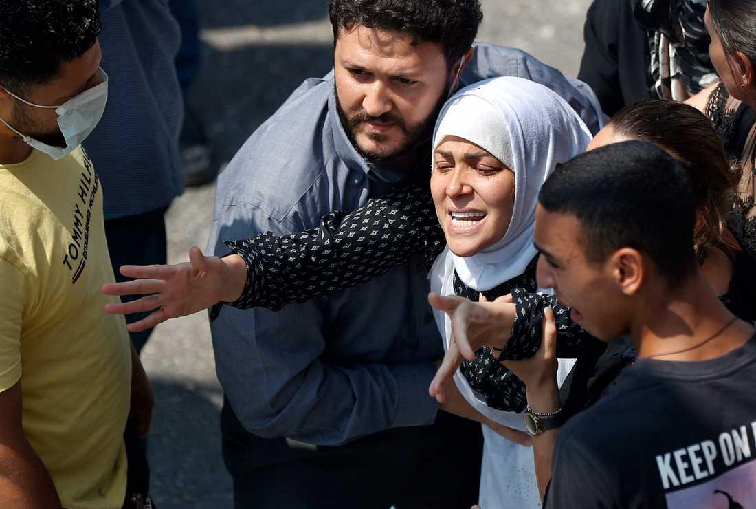 Die Witwe des Feuerwehrmanns Rami Kaaki, einer der zehn Feuerwehrleute, die während der Explosion ums Leben kamen, reicht während der Beerdigung in Beirut bis zum Sarg seines verstorbenen Mannes.