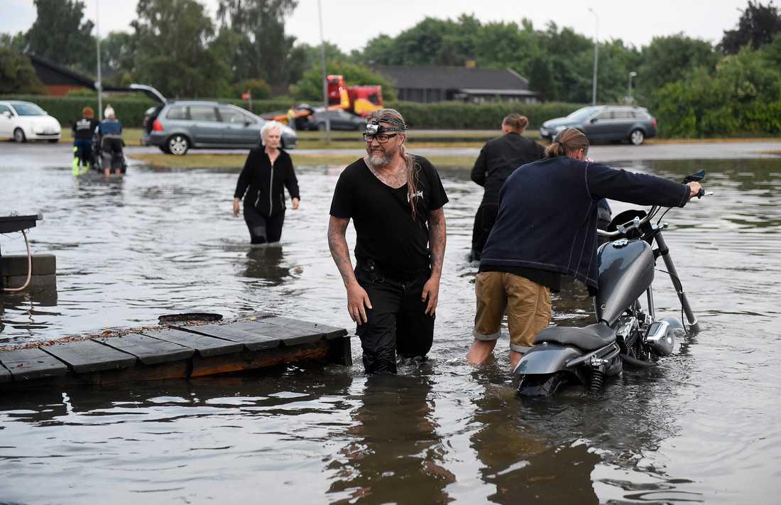 Kent Plateryd (mitten) övervakar då motorcyklar räddas undan hos Custom By Kent i ett översvämmat Bjuv efter att kraftiga åskskurar drabbat södra Sverige på onsdagen.