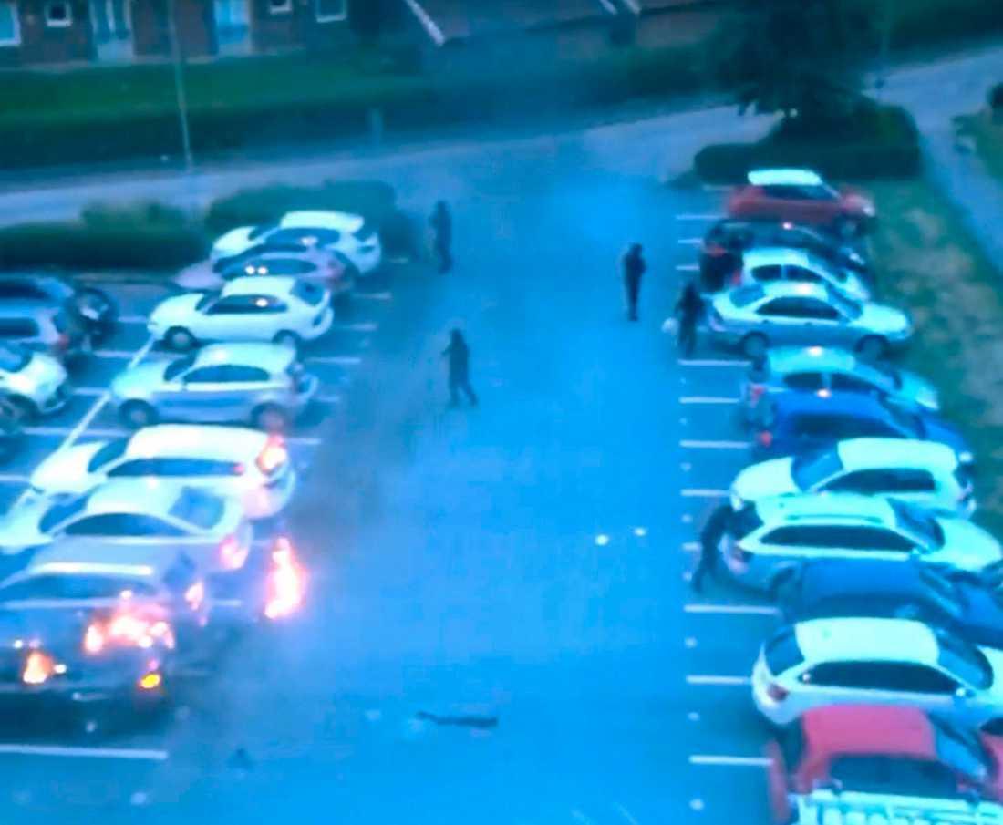 Svartklädda personer tänder eld på bilar vid Frölunda torg.
