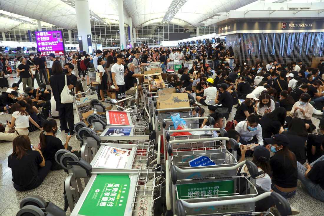 Demonstranter använder bagagevagnar för att hindra resenärer från att nå sina gater på Hongkongs flygplats.