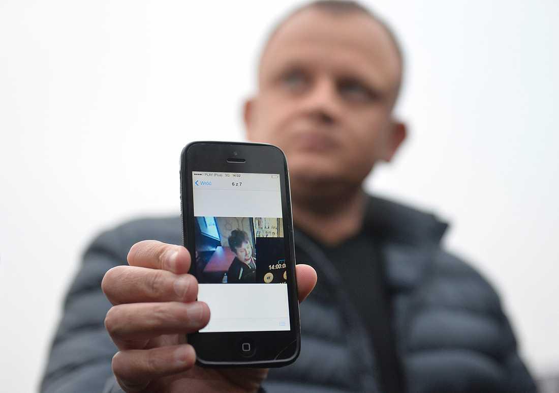 Ariel Zurawski, åkeriägare, visar upp den sista bilden som togs på sin kusin och anställde chaufför Lukasz Urban.