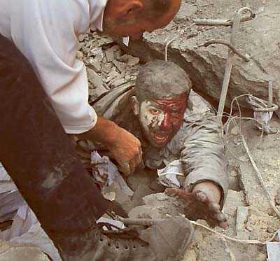 En skadad palestinsk man grävs fram efter ett bombanfall.
