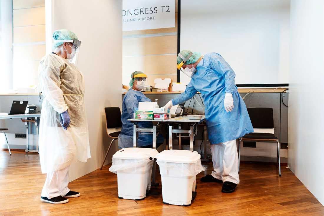 Vårdarbetare på Helsingfors flygplats väntar på inresande som ska testas för covid-19.