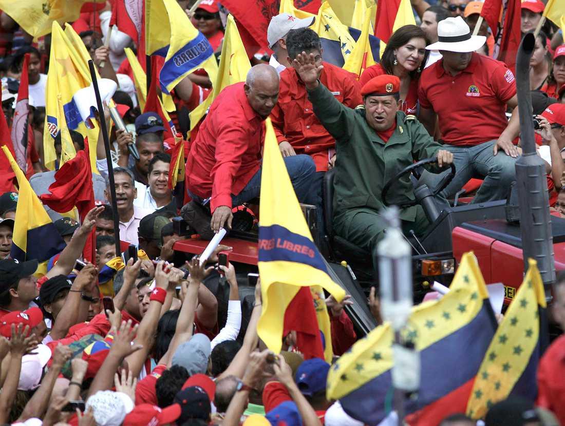 Chavez kör en traktor genom ett hav av supportrar i Caracas 2010.