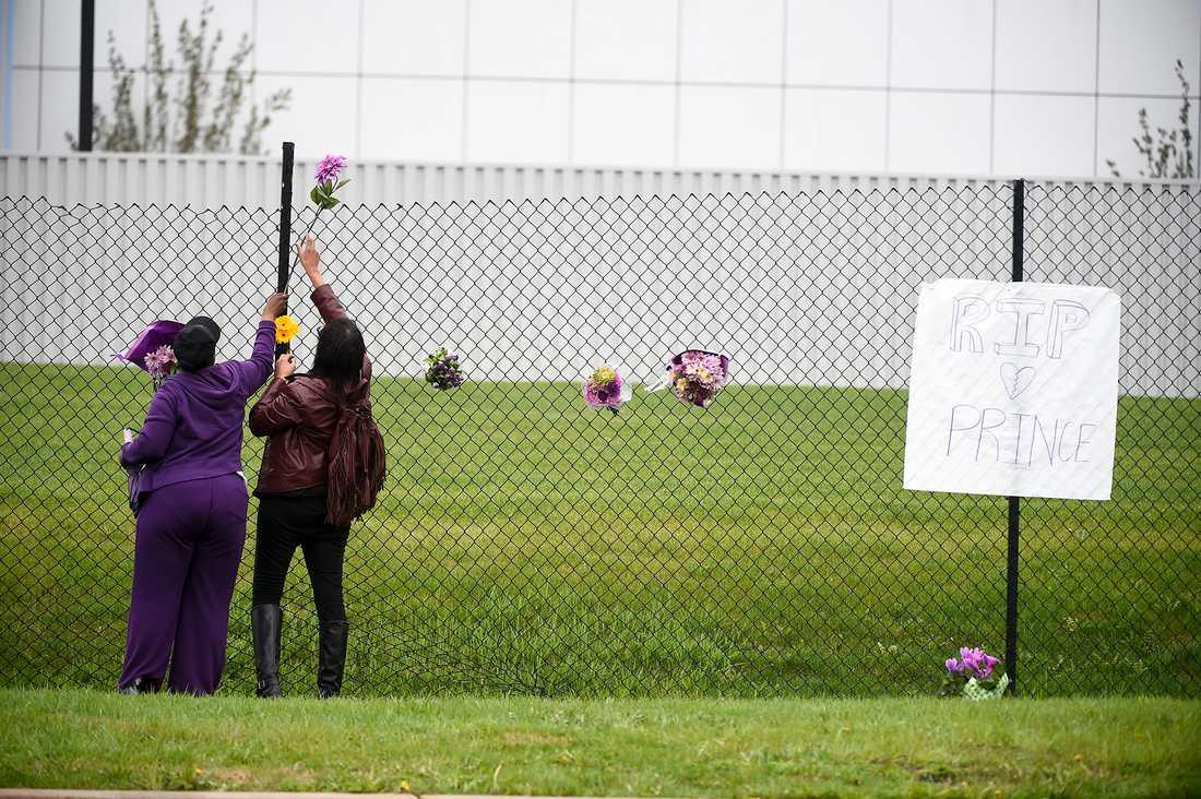 Två Princefans lämnar blommor utanför hans hem.