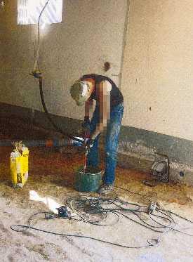 jobbar Mannen syns blanda cement och fixa på ett hus på bilderna.