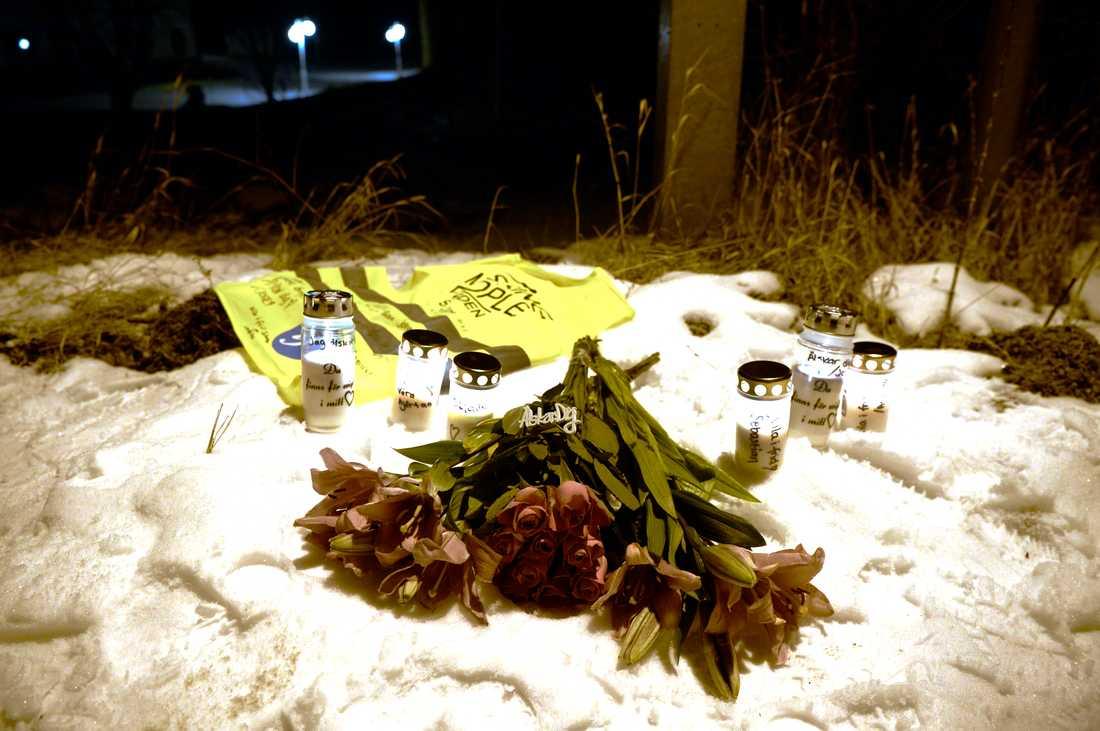 Vänner till kvinnan har lagt blommor och tänt ljus på platsen.