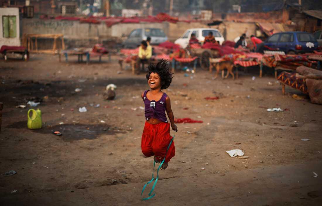 En flicka leker med ett hopprep intill en tillfällig bosättning i New Delhi, Indien. Landet har länge varit det land i världen med flest antal fattiga, men på senare år har andelen som lever i fattigdom minskat.