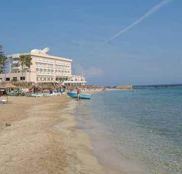 Turister hittar fortfarande till stranden i Famagusta, men det är inte många som förr.